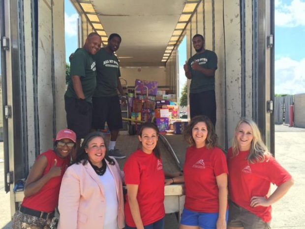 Junior League of Baton Rouge members receiving a large donation of diapers, wipes, and formula from the Junior League of New Orleans. All My Sons Moving and Storage helped deliver these items to the Cortana storefront, where JLBR members helped distribute items to families in need.