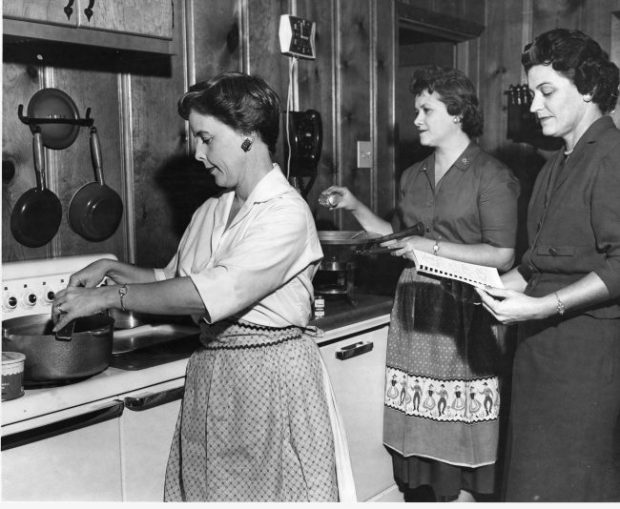 Testing the recipe for crabmeat casserole for River Road Recipes I. From left to right, Mrs. Lenton Sartain, Mrs. John Ferguson, and Mrs. John Gordon. Copyright retained by East Baton Rouge Parish Library.